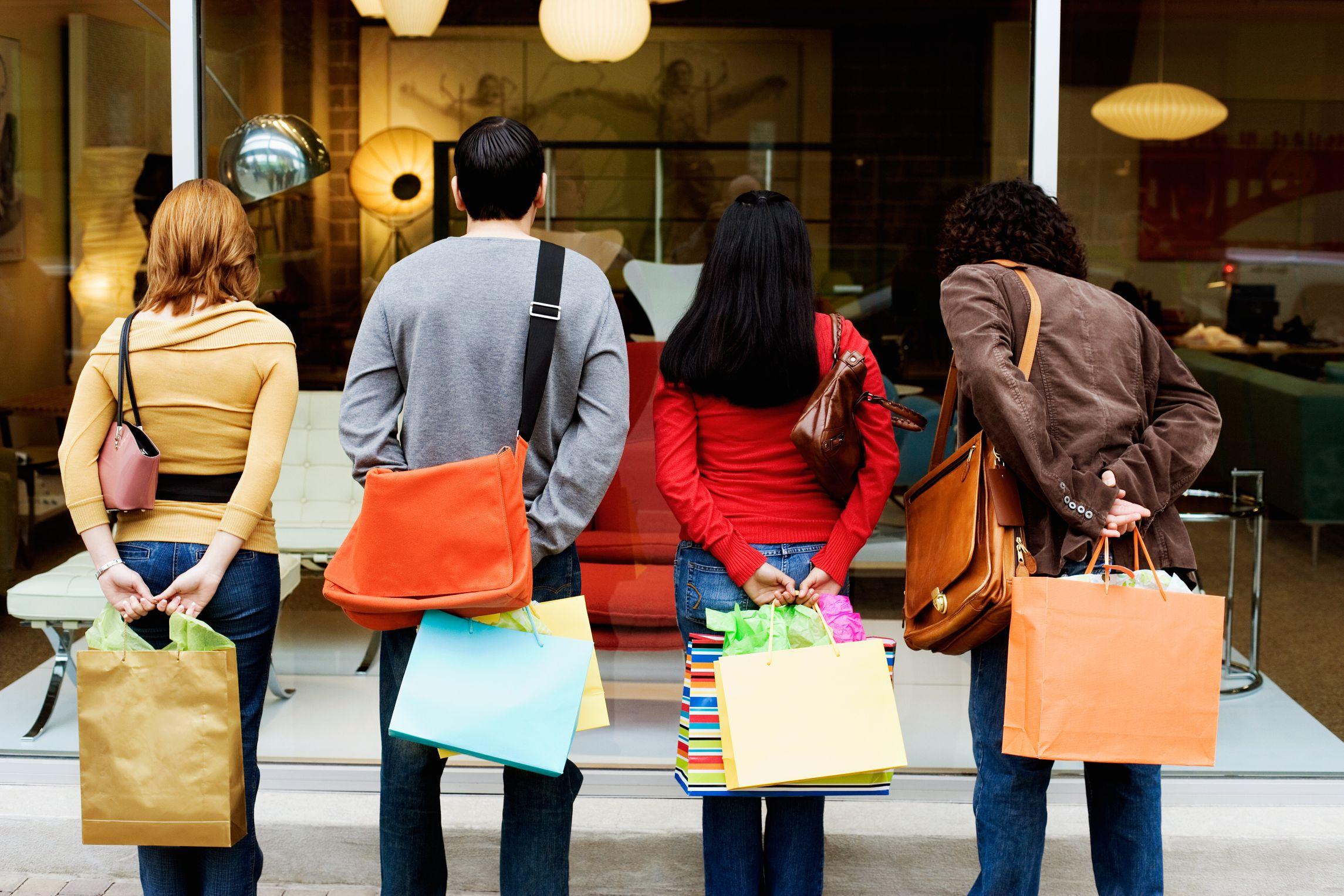 Cuatro-personas-con-bolsas-de-compra-mirando-un-escaparate